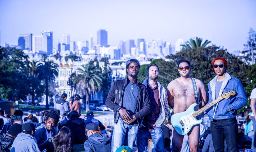 Members of Vinyl Spectrum standing in front of the LA city skyline.