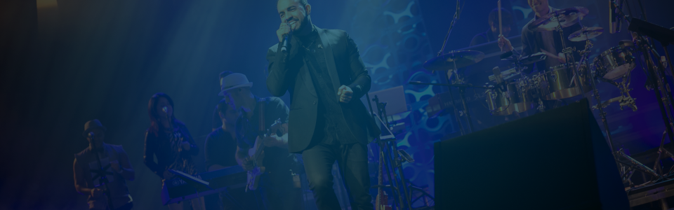 Still of a singer on stage with his band singing into a microphone in the PBS Fall Arts Festival. Flavorlab Score provided original custom music for the promo.