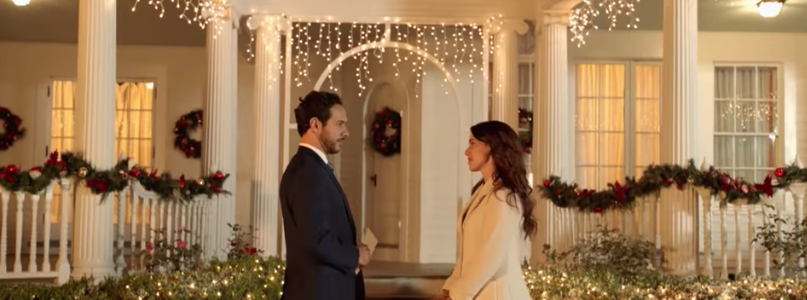 Still from Hallmark's Christmas at Pemberley Manor of Jessica Lowndes and Michael Rady looking at each other in front of a full decorated mansion. Flavorlab Sound provided sound design, voice over recording, and mix for the film.
