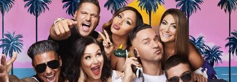The cast of Jersey Shore family vacation posing in front of a fake beach backdrop with pink sky and palm trees