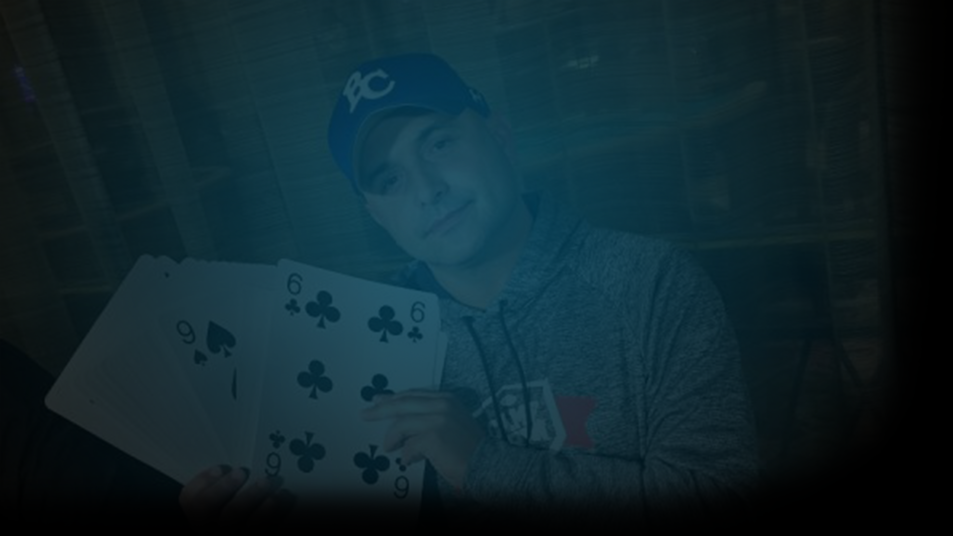 Still of Craig Carton holding giant playing card and looking at the camera in a grey hoodie and blue baseball cap. Flavorlab Score provided original score for documentary, Wildcard, on HBO, about Carton's radio days, double life, and arrest.